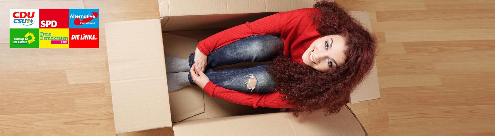 Junge Frau sitzt im Umzugskarton