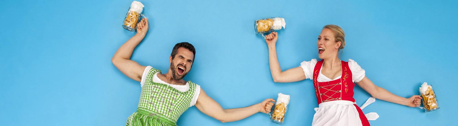 Mann und Frau tanzen in Dirndl mit Bierkrügen in den Händen