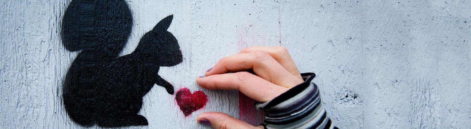 Ein Graffiti Eichhörnchen hat ein Herz in der Pfote- eine menschliche Hand scheint es zu greifen