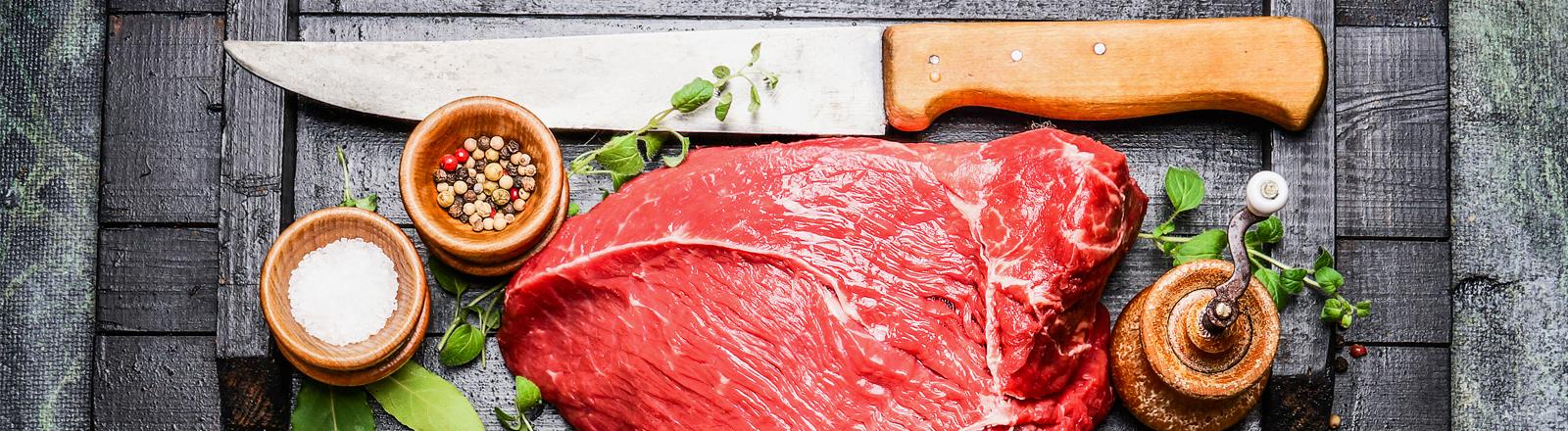 Ein Stück Fleisch auf einem Brett, angerichtet neben einem Messer, Pfefferkörnern und Salz