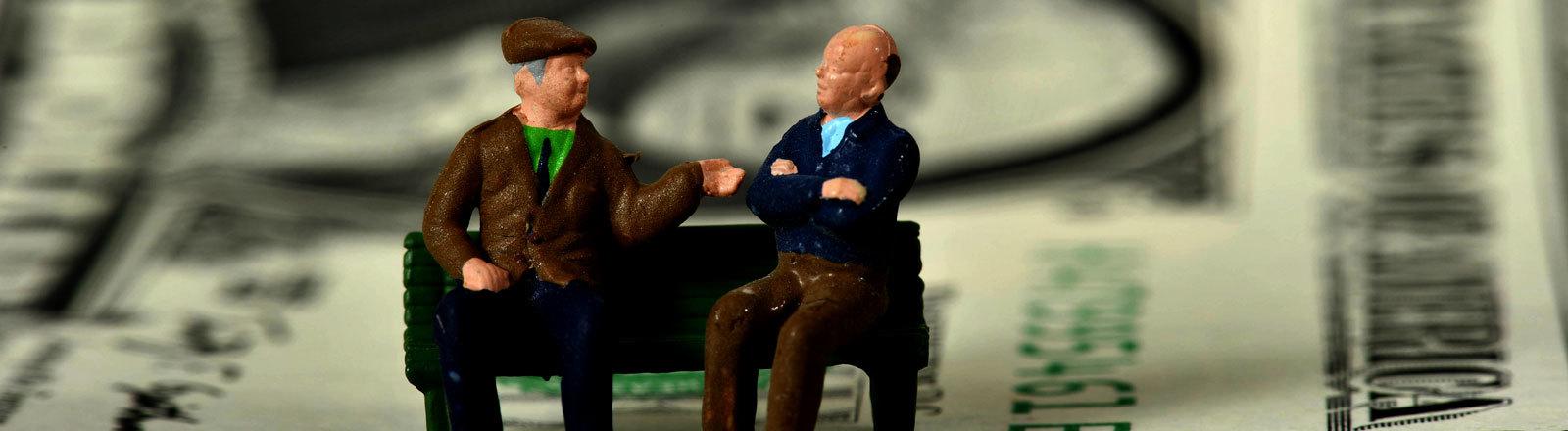 Zwei Figuren, die Rentner darstellen, sitzen auf einer Bank