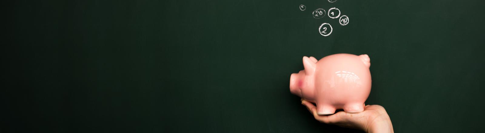 Ein Sparschwein vor einer Tafel, von oben fliegen mit Kreide gemalte Münzen in den Schlitz
