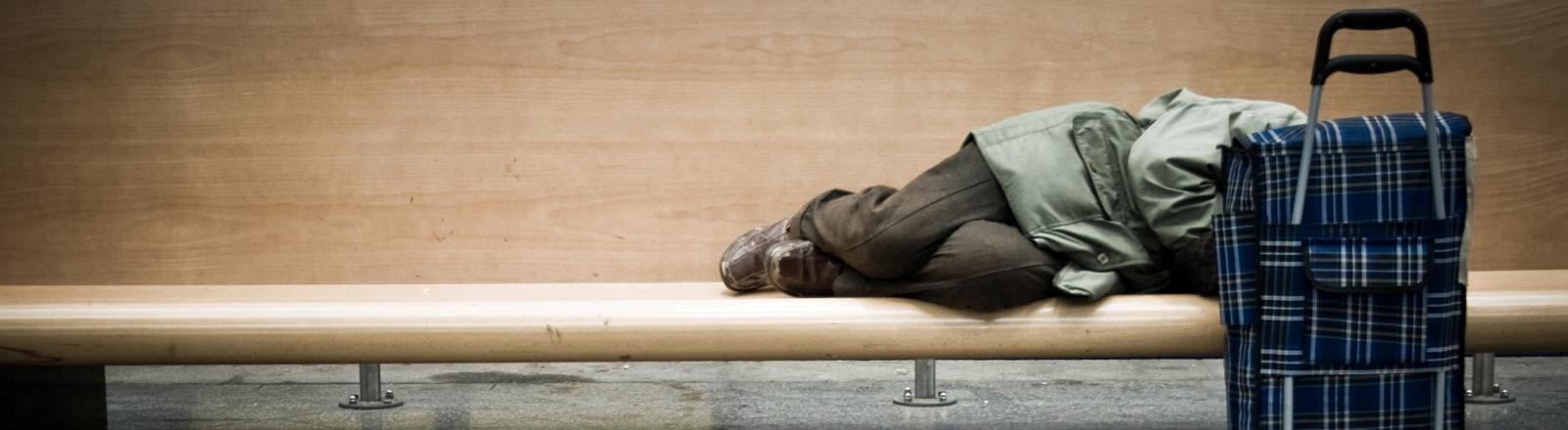 Ein Obdachloser schläft auf einer Parkbank.