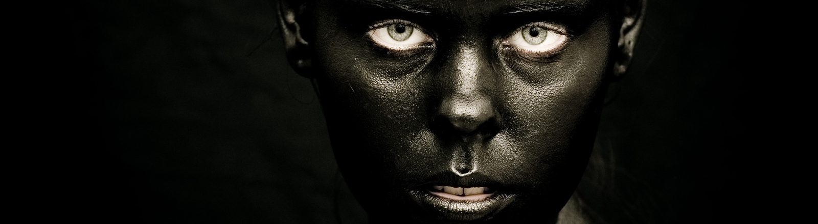 Eine Frau hat sich das Gesicht schwarz angemalt.
