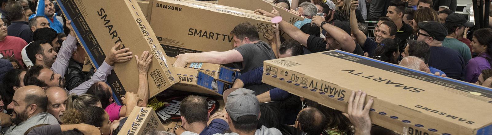 Menschen reißen sich am Black Friday um die Produkte im Kaufhaus.
