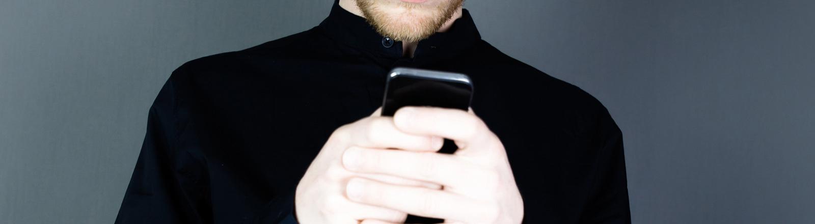 Ein Mann hält ein Handy in seinen Hand und blickt darauf. Er trägt ein schwarzes Hemd. Sein Gesicht ist nicht zu erkennen.
