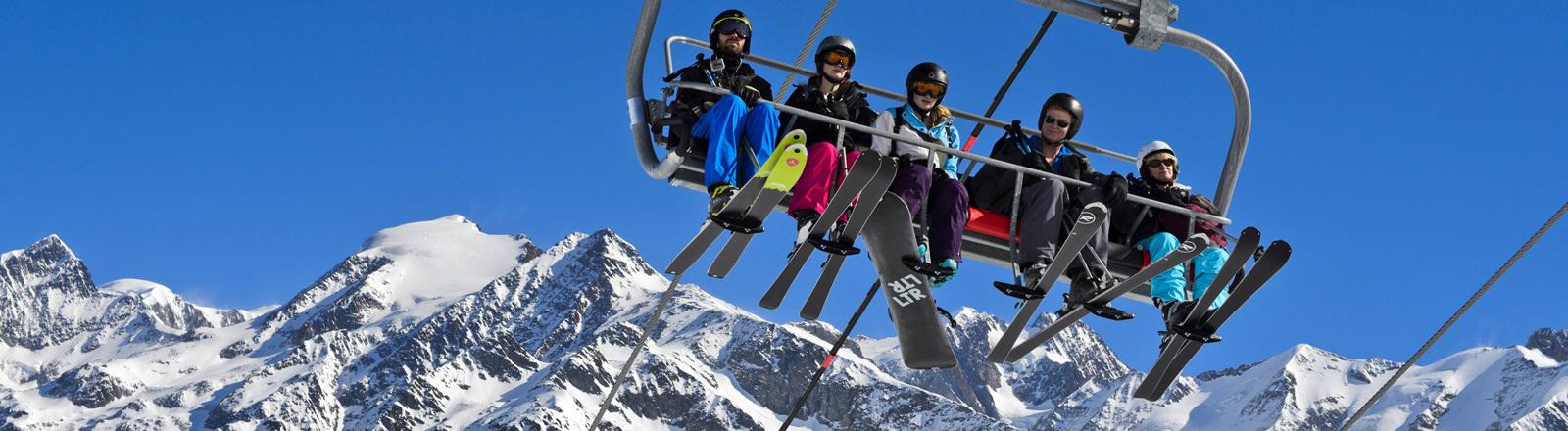 Auf einem Skilift sitzen fünf Personen in Skikleidung und mit Skiern sowie Snowboard. Im Hintergrund verschneite Berge.