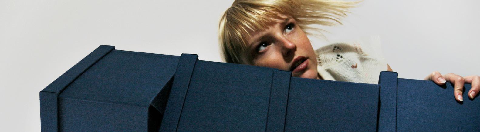 Eine Frau schaut hinter einem Stapel blauer Schachteln hervor.