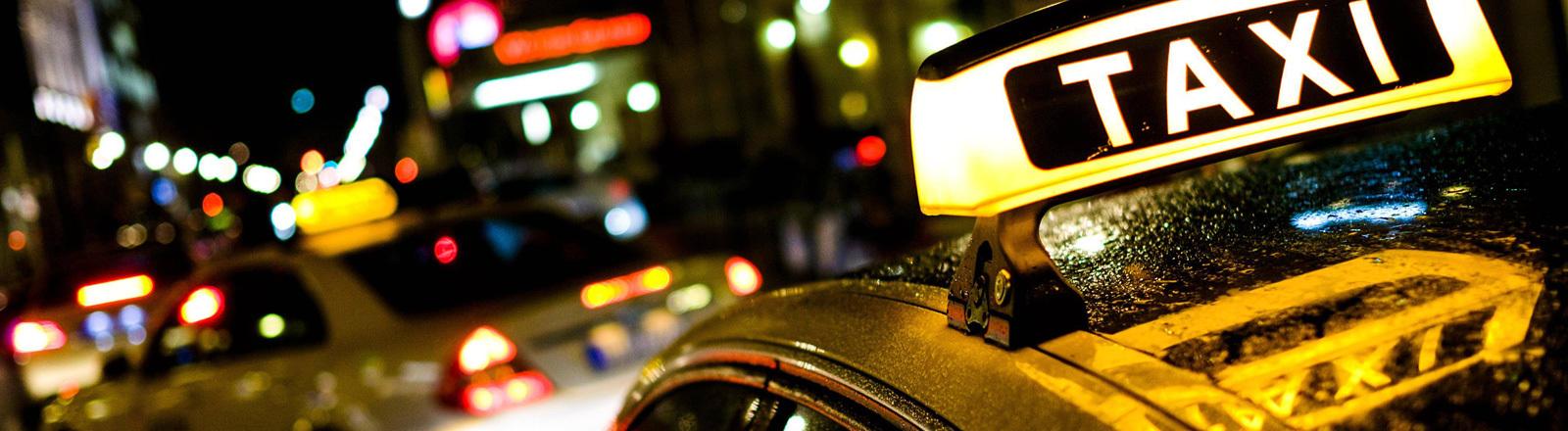 Zwei Taxis stehen nachts im Straßenverkehr. Die Lampen der Autos und die Straßenlampen leuchten.