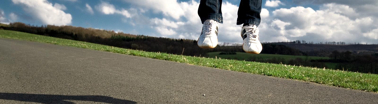 Zwei Füße stehen in der Luft über der Straße