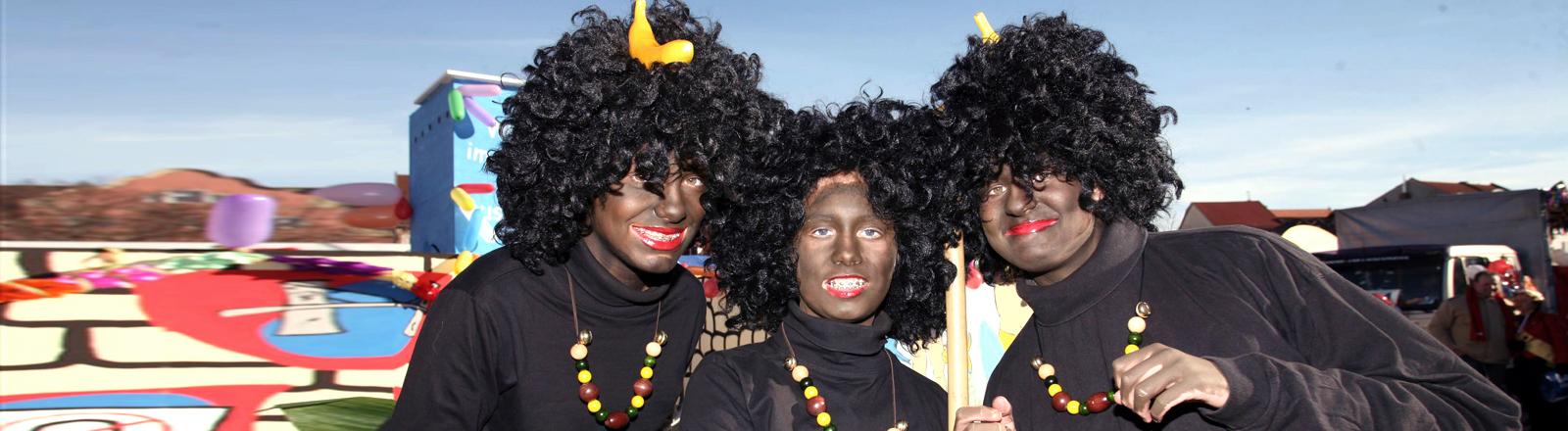 schwarz geschminkte Karnevalistinnen mit Afro-Perücke