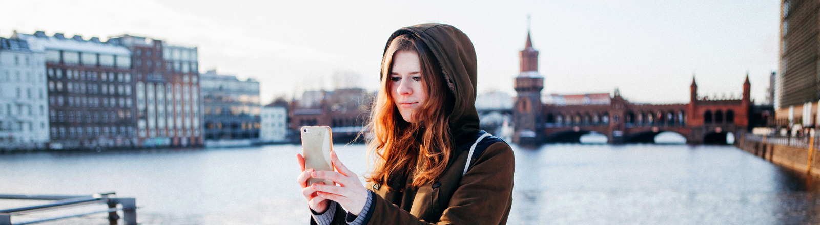Frau macht Selfie vor der Berliner Oberbaumbrücke