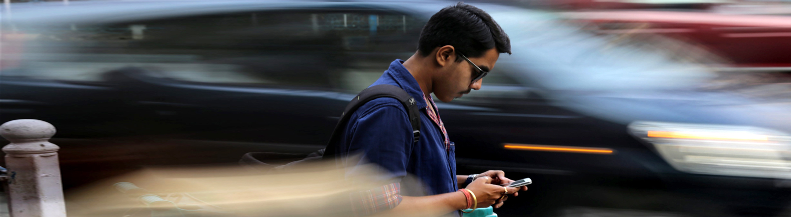 Mann am Straßenrand tippt auf Smartphone