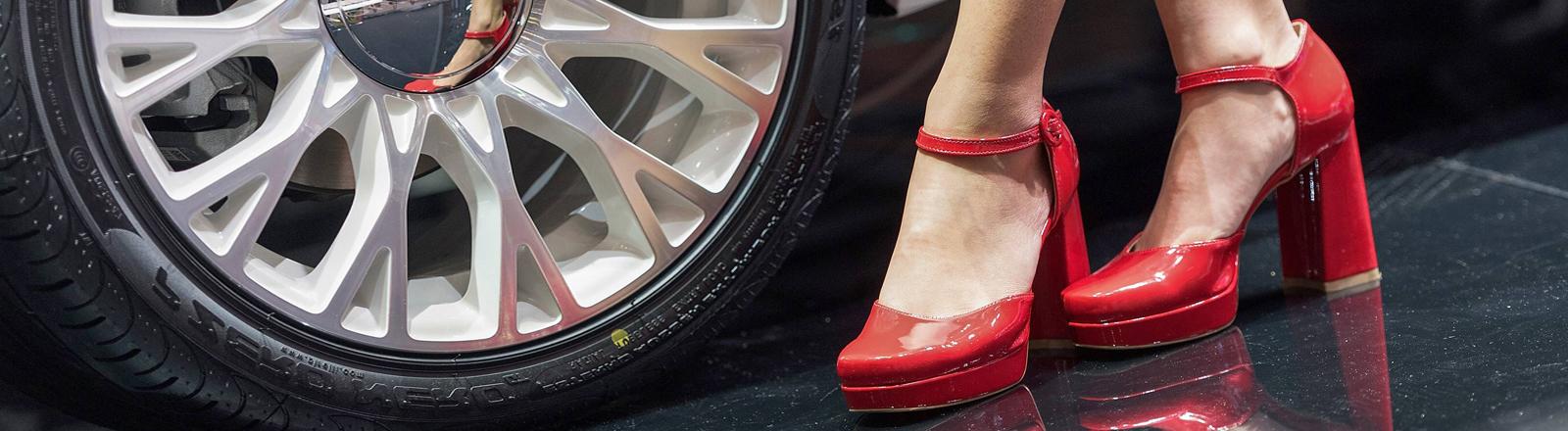 Frauen-Füße in roten Heels vor Autofelge