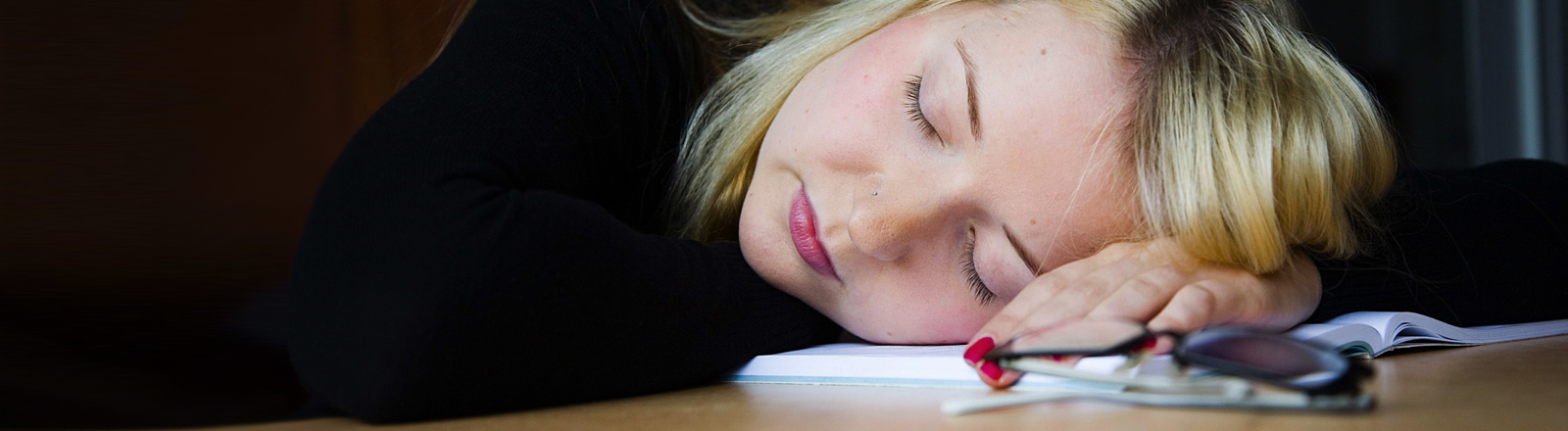 Frau schläft auf ihrem Schreibtisch