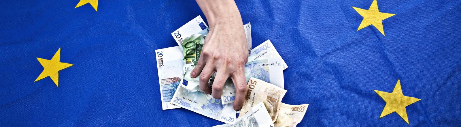 Hand greift nach Euro-Scheinen auf einer EU-Flagge