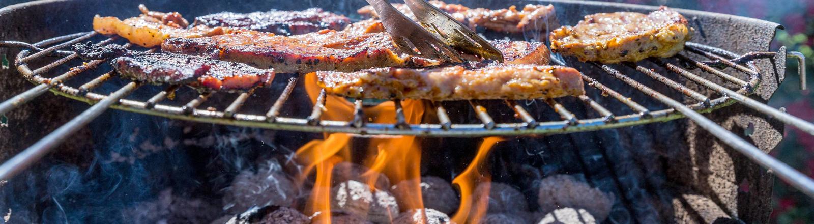 Holzkohle-Grill mit Fleisch auf dem Rost
