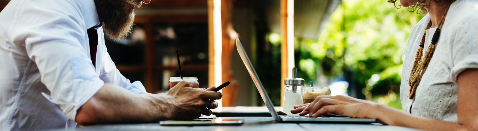 Mann und Frau am Tisch mit Smartphone und Laptop