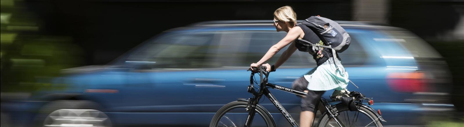 Fahrradfahrerin neben Auto