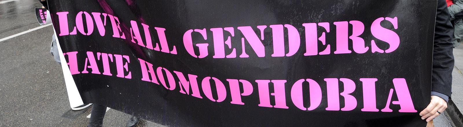 Auf einem Plakat steht Love all Genders hate homophobia