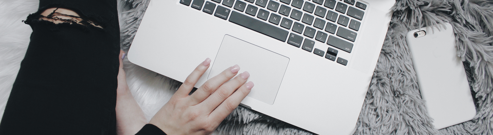 die Hand einer Frau auf dem Trackpad ihres Laptops