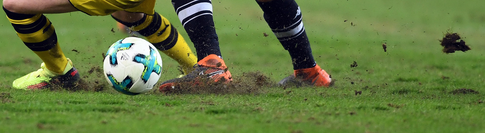 Zwei Bundesligsten bei einem Match auf einem Rasen im Stadion.