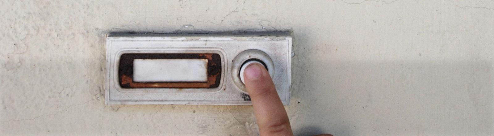 Ein Finger drückt einen Klingelknopf.