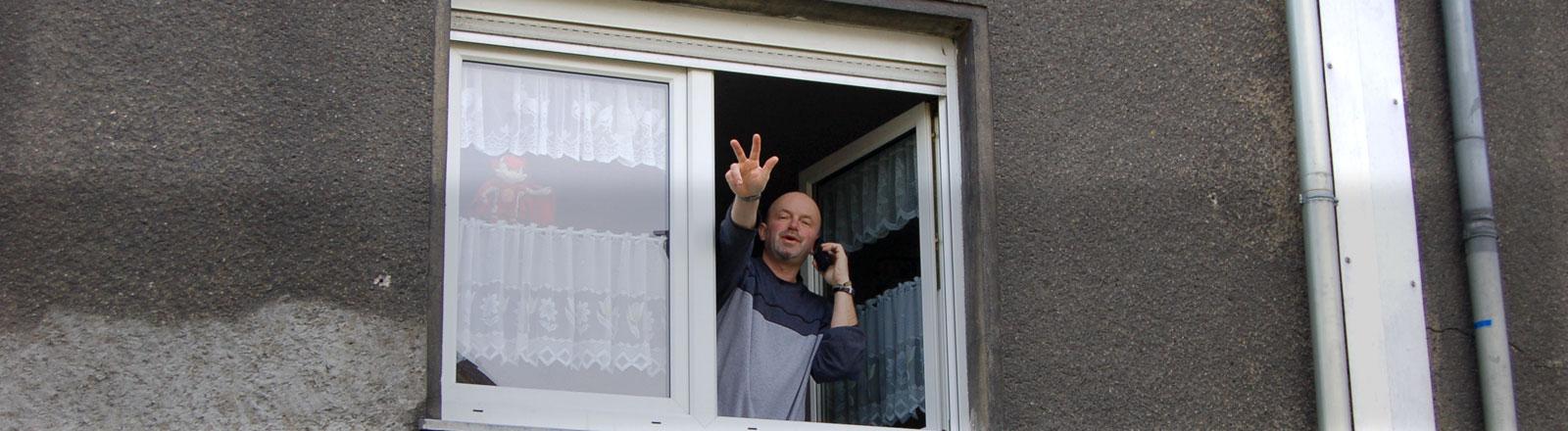 Ein Mann hält ein Telefon an sein Ohr und winkt aus einem Fenster.