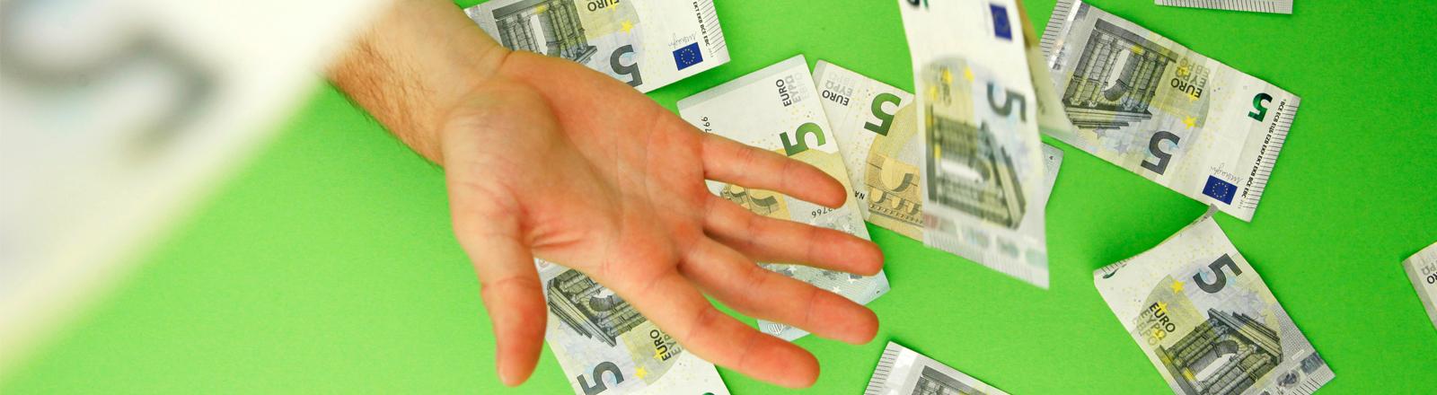 Vor einem grünen Hintergrund fliegen 5-Euro-Scheine durch die Luft, eine Hand versucht, sie zu fangen.