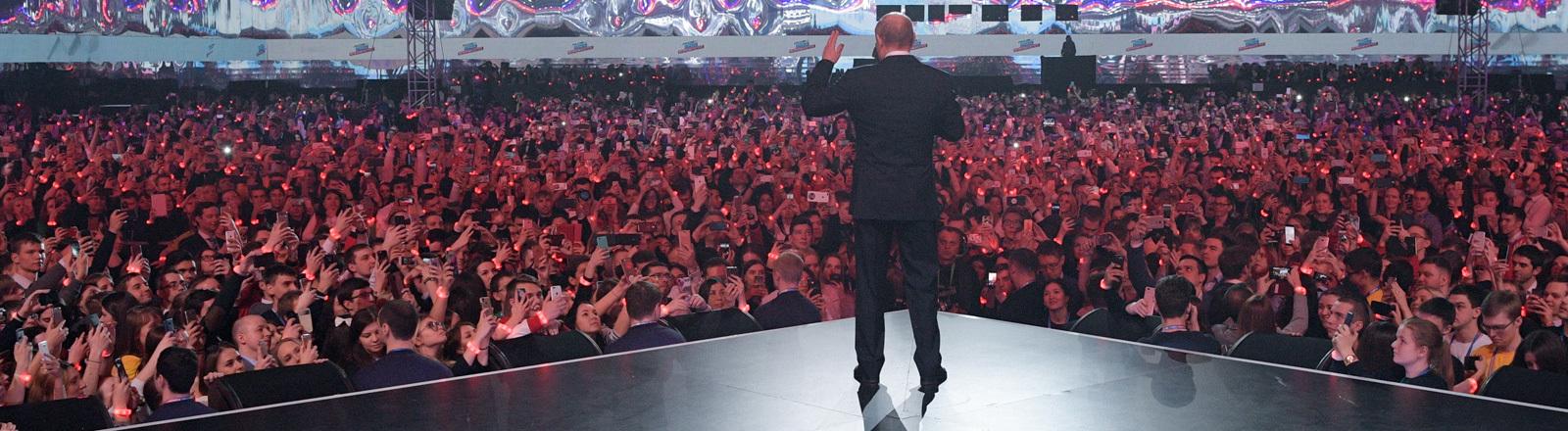 Bei einer Veranstaltung vor großem Publikum spricht Putin; er ist von hinten zu sehen, wie er spricht; Foto: dpa