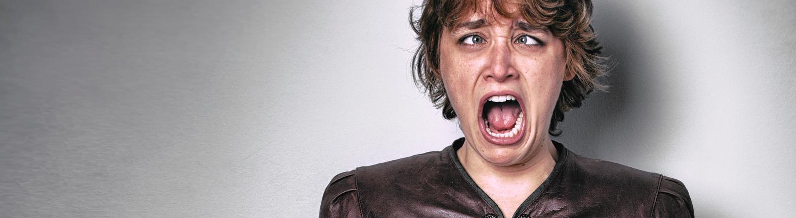 Eine Frau zieht eine Schrei-Grimasse.