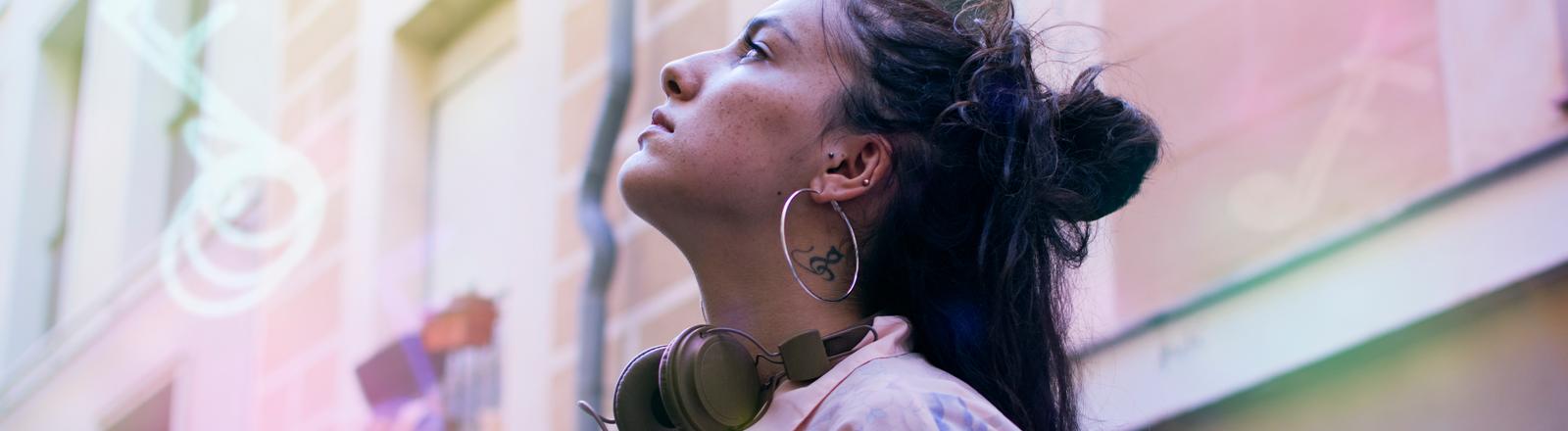 Eine Frau hat Kopfhörer um den Hals hängen und schaut in die Luft