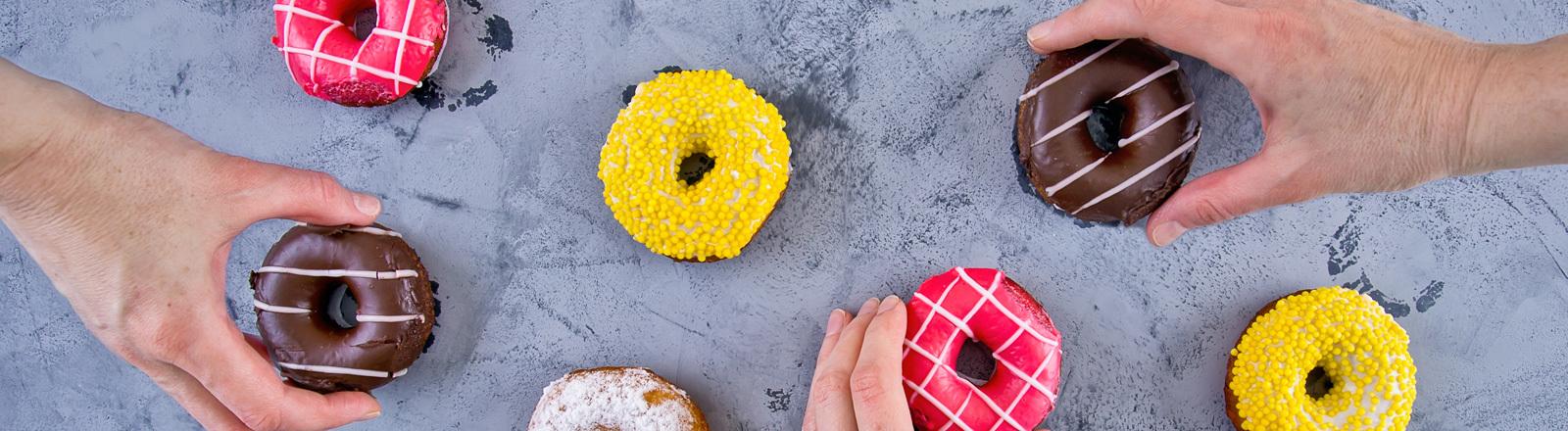 Drei Hände greifen nach bunten Donuts, die auf einem Tisch liegen.