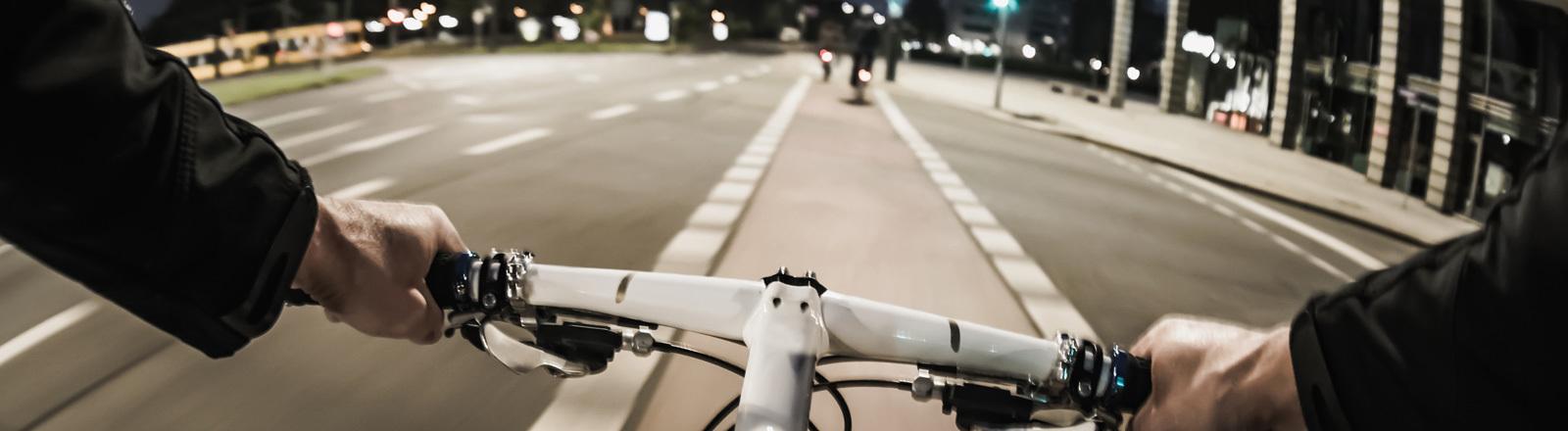 Ein Fahrradfahrer fährt durch die Stadt. Die Kamera hat seine Perspektive, der Blick fällt auf den Fahrradweg.
