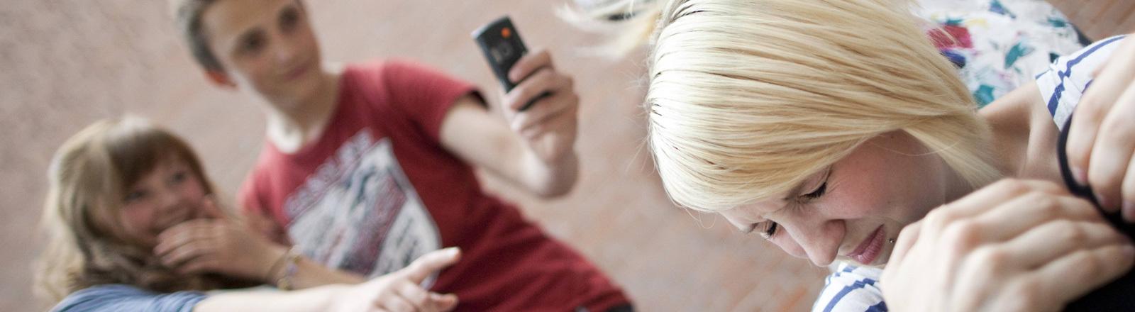 Symbolfoto: Ein Mädchen wir von Gleichaltrigen gehänselt und dabei mit einem Smartphone fotografiert.