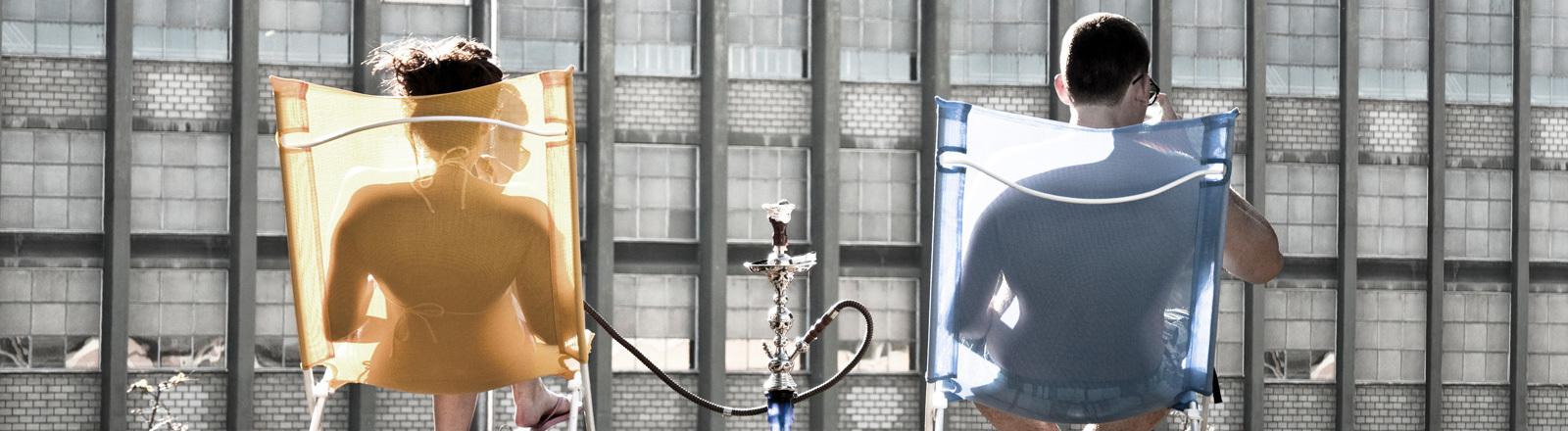 Paar sitzt auf Terrasse und raucht Wasserpfeife.