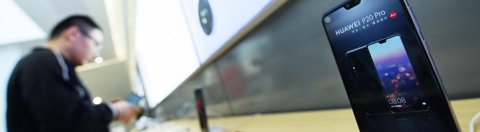 In der chinesischen Stadt Hangzhou steht ein Kunde in einem Huawei-Laden und schaut sich ein Smartphone an.