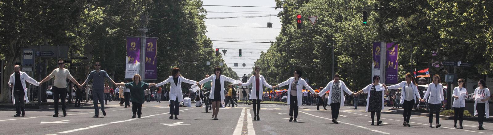 Auf einer Straße in Eriwan laufen Klinikangestellte in weißen Kitteln. Sie halten sich an den Händen. Auf der Straße ist kein Verkehr.