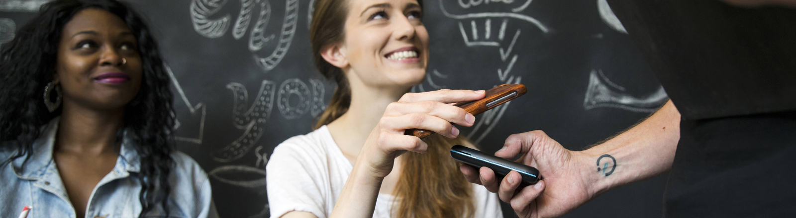 Eine Frau bezahlt mit ihrem Smartphone.