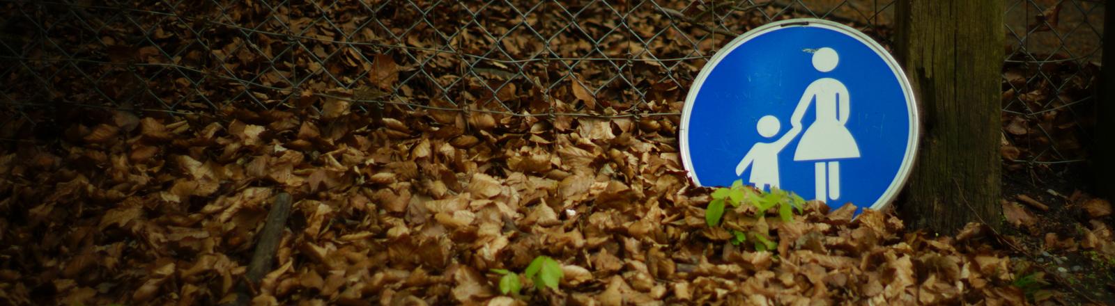 """Ein """"Mutter-und-Kind""""-Straßenschild liegt im Laub."""