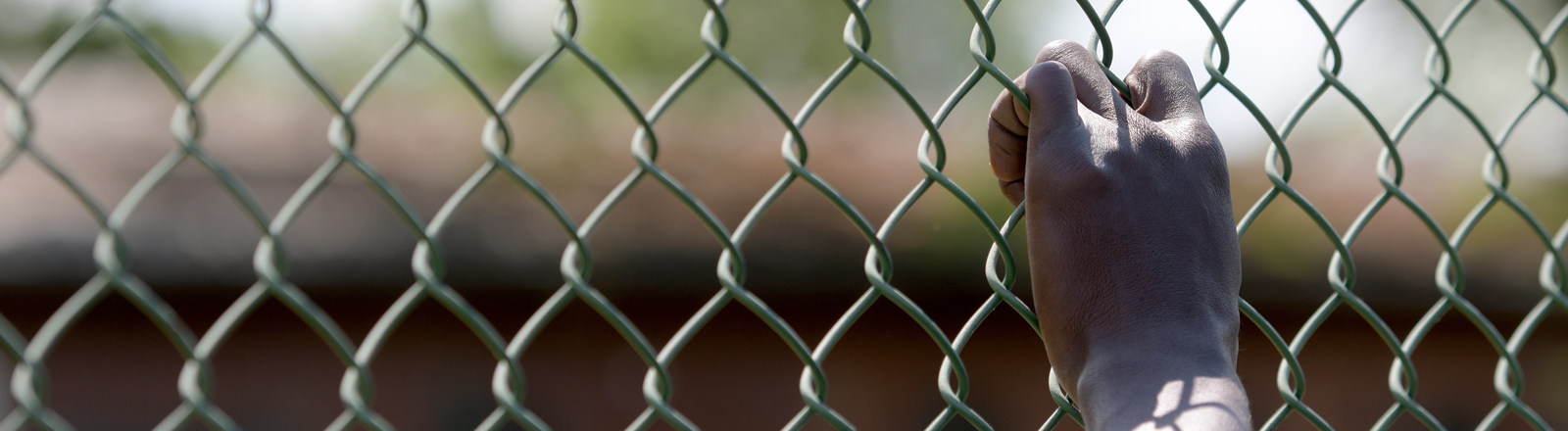 Eine Hand hält sich an einem Zaun fest.