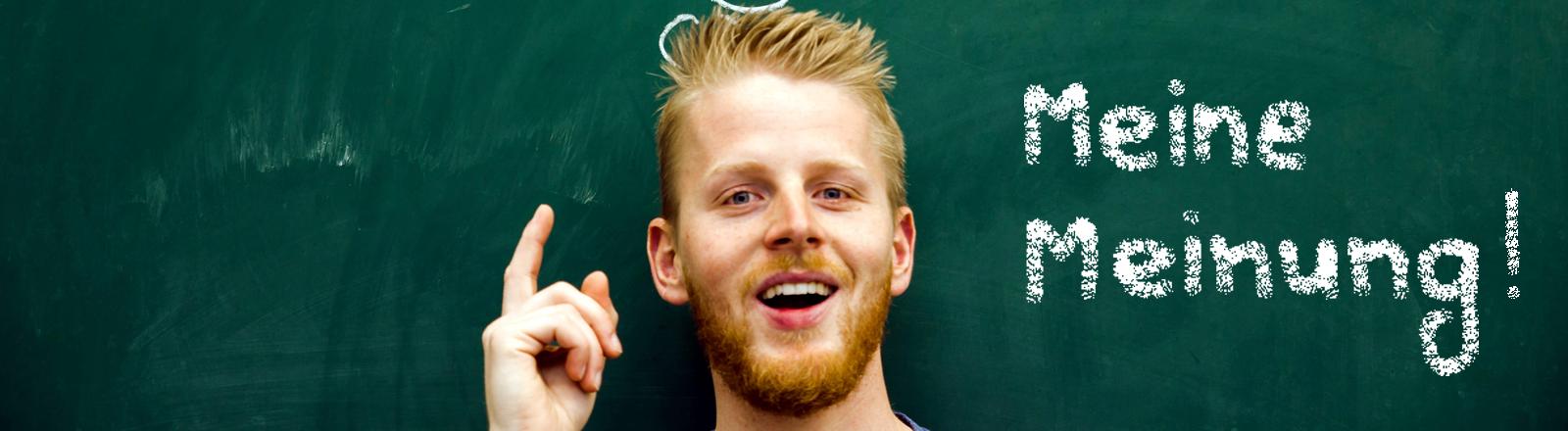 Ein junger Mann steht vor einer Tafel mit erhobenem Zeigefinger und lächelt