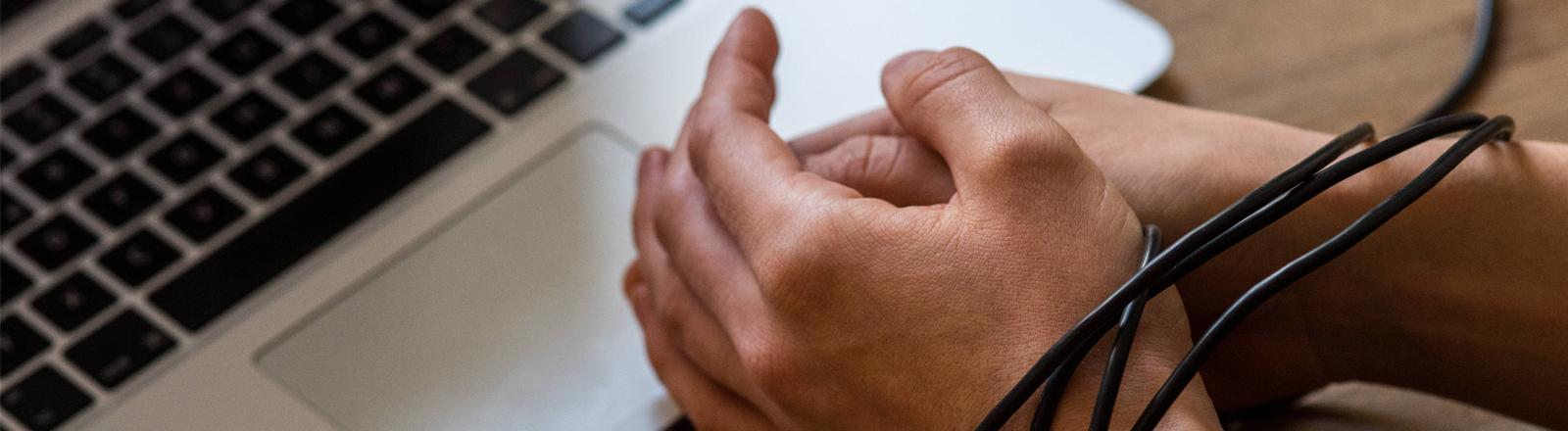 Durch das Kabel einer Computermaus gefesselte Hände vor einer Tastatur