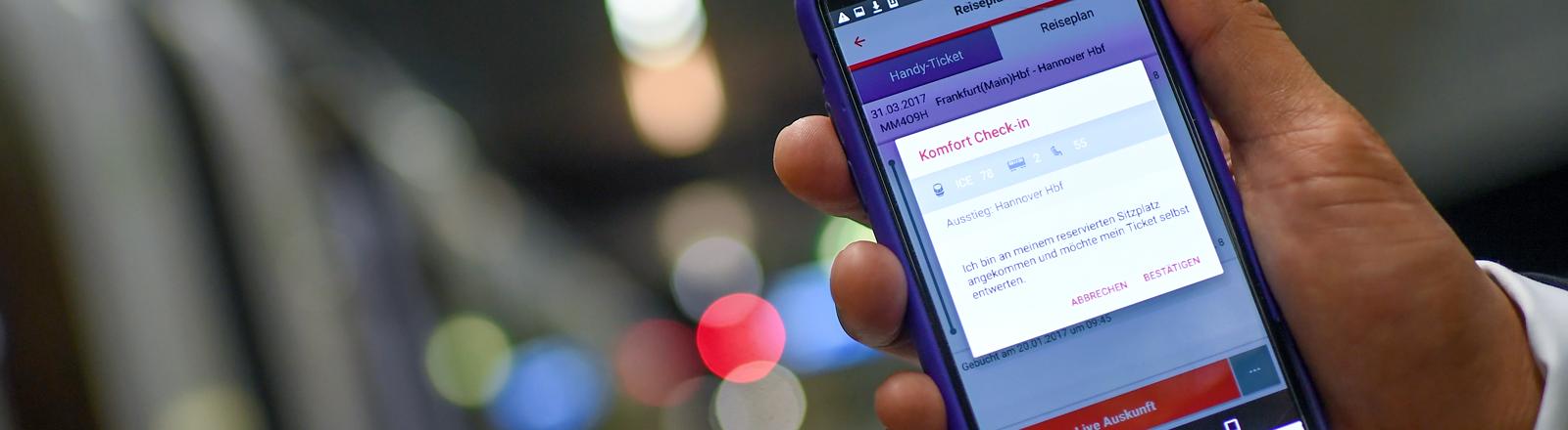 Nahaufnahme einer Hand, die ein Smartphone mit der Bahn-App in die Kamera hält vor einem ICE