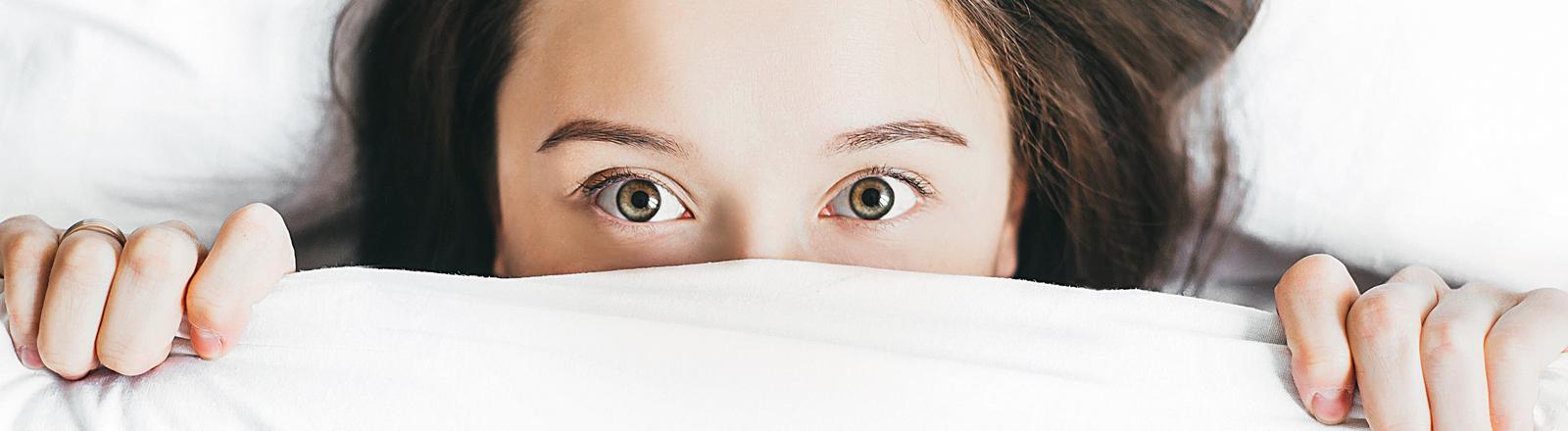 Eine Frau liegt im Bett und hat die Bettdecke bis über die Nase hochgezogen