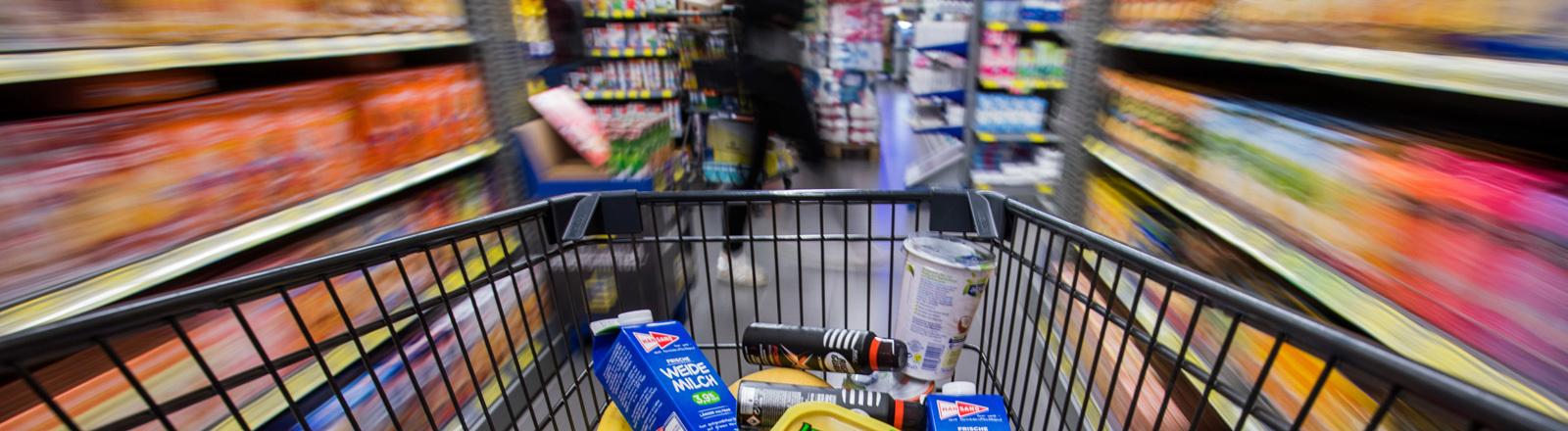 Ein Einkaufswagen mit Lebensmitteln wird durch die Regalreihen in einem Supermarkt geschoben; Foto: dpa
