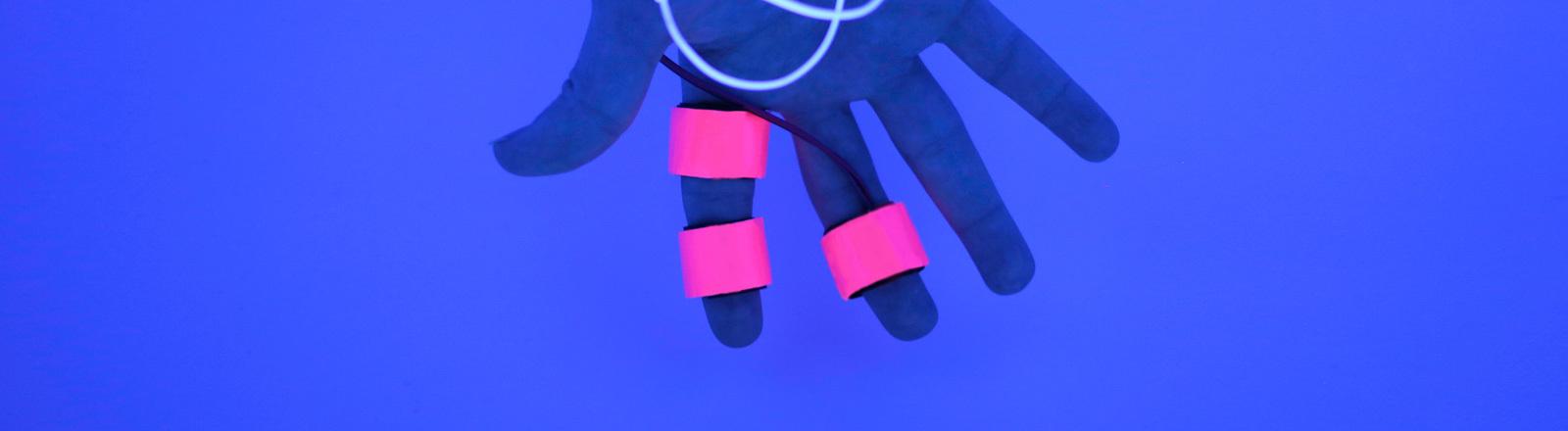 An zwei Fingern sind Sensoren angebracht.