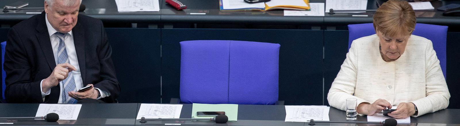 Am 03.07.2018 nehmen Kanzlerin Merkel und Innenminister Seehofer an der Plenarsitzung im Bundestag teil. Sie sitzen nebeneinander, zwischen ihnen bleibt zunächst ein Stuhl leer.