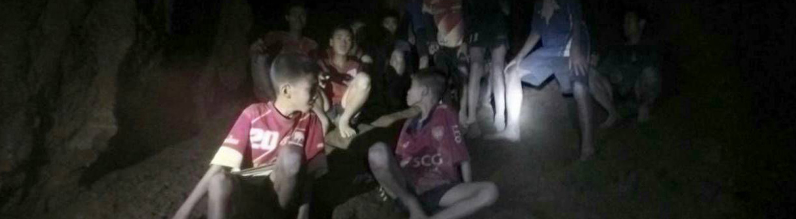 Blick in die Höhle, in der die Fußballmannschaft und ihr Trainer gefangen sind. Ihre Gesichter werden von Taschenlampen der Rettungskräfte angestrahlt (02.07.2018)