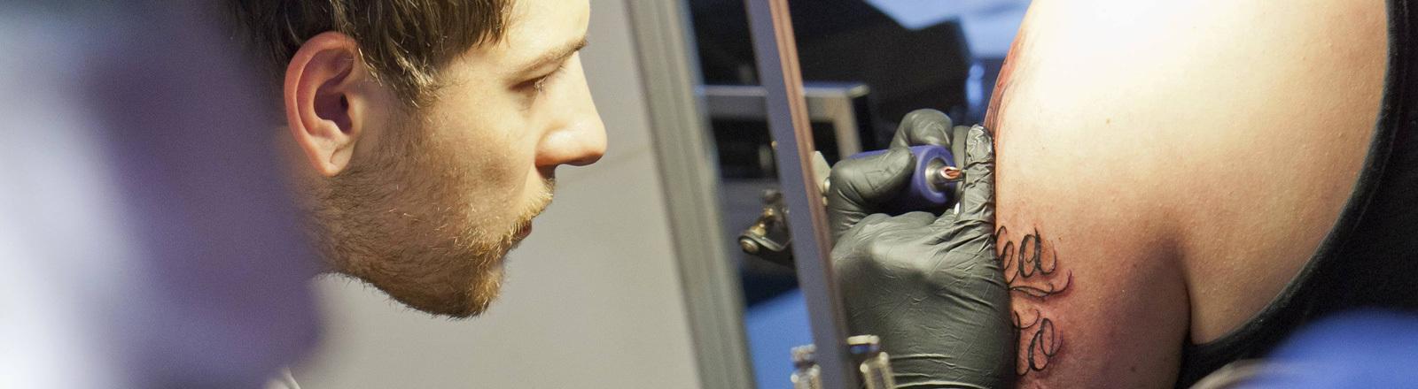 Ein Tätowierer bei der Arbeit; er sticht auf den Oberarm eines Mannes ein Tattoo.